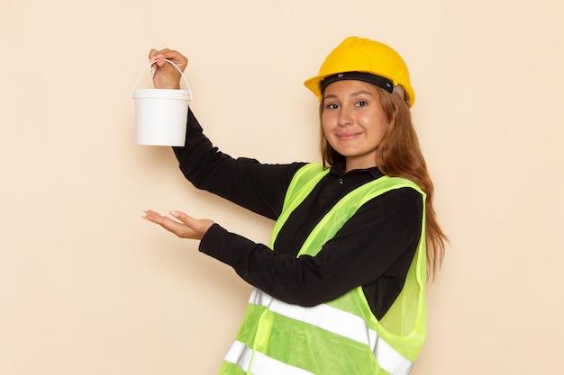 Widok z przodu żeński konstruktor w żółtym kasku czarnej koszuli trzyma farbę na białej ścianie kobieta architekta konstruktora