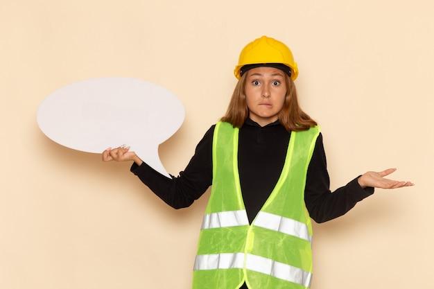 Widok z przodu żeński konstruktor w żółtym kasku trzymający duży biały znak stwarzających na białej ścianie architekt kobieta
