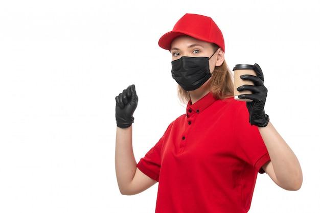 Widok z przodu żeński kurier w czerwoną koszulę czerwoną czapkę czarne rękawiczki trzyma kawę na białym