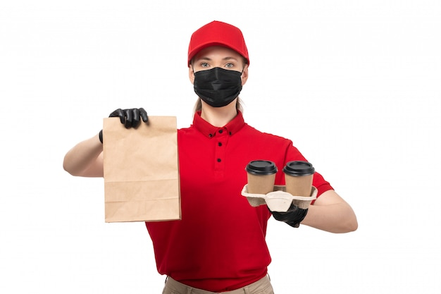 Widok z przodu żeński kurier w czerwonej koszuli, czerwoną czapkę, czarne rękawiczki i czarną maskę, trzymając pakiet z jedzeniem i filiżanki kawy na białym tle