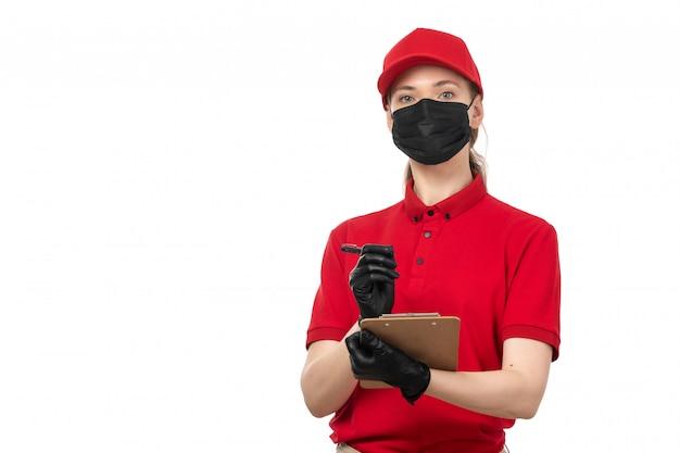 Widok z przodu żeński kurier w czerwonej koszuli, czerwoną czapkę, czarne rękawiczki i czarną maskę, zapisujący zamówienia na białym tle
