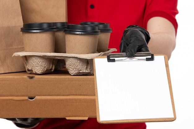 Widok z przodu żeński kurier w czerwonej koszuli, czerwonej czapce, czarnych rękawiczkach i czarnej masce, trzyma filiżanki kawy i opakowania żywności z notatnikiem
