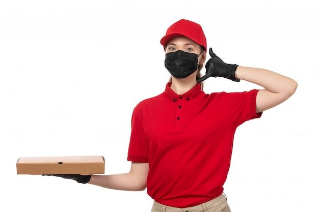 Widok z przodu żeński kurier w czerwonej koszuli, czerwonej czapce, czarnych rękawiczkach i czarnej masce, trzyma pudełko pizzy pozowanie na białym tle
