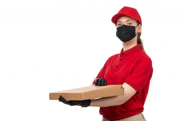 Widok z przodu żeński kurier w czerwonej koszuli, czerwonej czapce, czarnych rękawiczkach i czarnej masce, trzymając pudełko po pizzy na białym tle