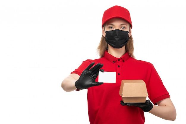 Widok z przodu żeński kurier w czerwonej koszuli, czerwonej czapce i czarnej masce, trzyma białą kartę i paczkę z jedzeniem