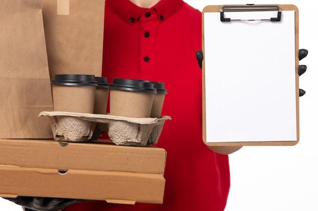 Widok z przodu żeński kurier w czerwonej koszuli i czarnych rękawiczkach trzyma opakowania żywności i kawę z notatnikiem