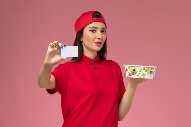 Widok z przodu żeński kurier w czerwonej pelerynie mundurowej z miską dostawy i białą kartą na rękach na jasnoróżowej ścianie, jednolity pracownik dostawy pracy