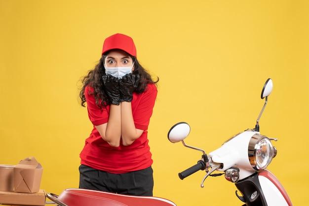 Widok z przodu żeński kurier w czerwonym mundurze i masce na żółtym tle covid - pandemia pracownika usługi dostarczania pracy
