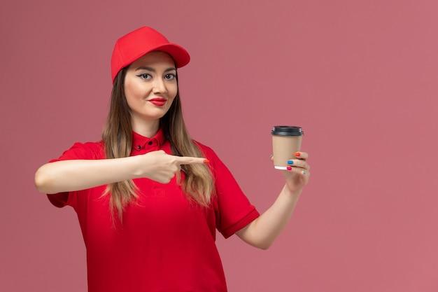 Widok z przodu żeński kurier w czerwonym mundurze i pelerynie trzyma filiżankę kawy dostawy na różowej podłodze świadczenie usług jednolity pracownik