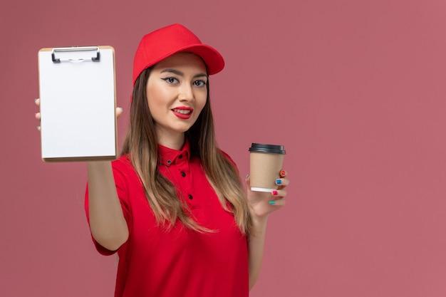 Widok z przodu żeński kurier w czerwonym mundurze i pelerynie trzyma filiżankę kawy dostawy z notatnikiem na jasnoróżowym tle mundur dostawy pracy usługi