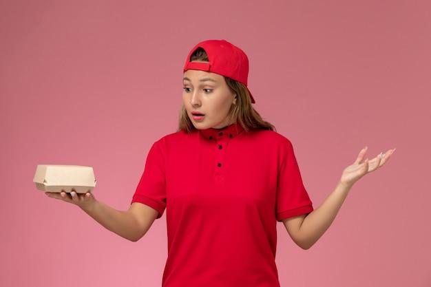 Widok z przodu żeński kurier w czerwonym mundurze i pelerynie trzyma pakiet żywności dostawy na różowym tle jednolite pracownik służbowy dostawczy