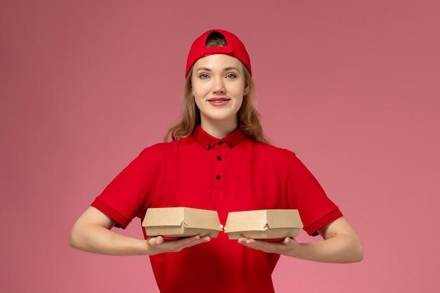 Widok z przodu żeński kurier w czerwonym mundurze i pelerynie trzymający małe paczki żywnościowe z uśmiechem na różowej ścianie, jednolita praca firmy świadczącej usługi dostawcze
