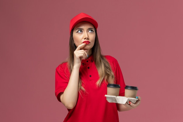 Widok z przodu żeński kurier w czerwonym mundurze trzyma brązowe filiżanki kawy dostawy i myśli na różowym tle świadczenie usług jednolite stanowisko pracownika firma kobieta
