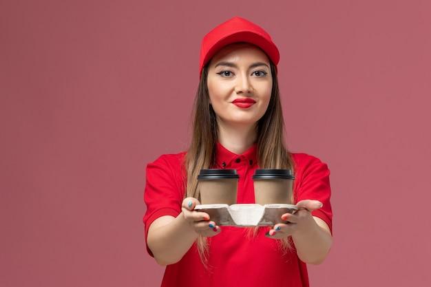 Widok z przodu żeński kurier w czerwonym mundurze, trzymając brązowe filiżanki kawy dostawy i uśmiechając się na różowym tle