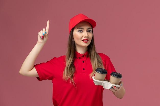 Widok z przodu żeński kurier w czerwonym mundurze, trzymając brązowe filiżanki kawy dostawy na jasnoróżowym tle firma świadcząca usługi w mundurze pracownika