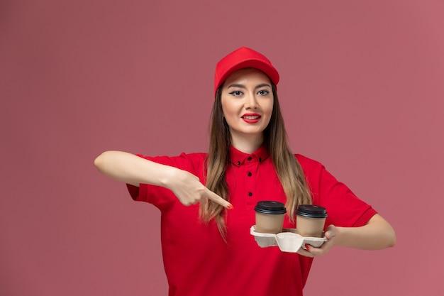 Widok z przodu żeński kurier w czerwonym mundurze, trzymając brązowe filiżanki kawy dostawy na różowym tle