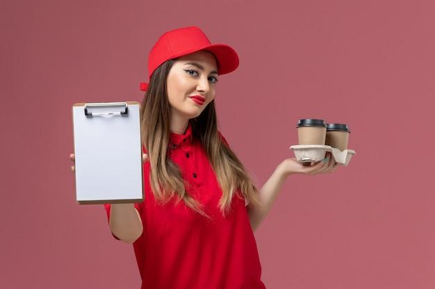 Widok z przodu żeński kurier w czerwonym mundurze, trzymając filiżanki kawy dostawy i notatnik uśmiechnięty na różowym tle