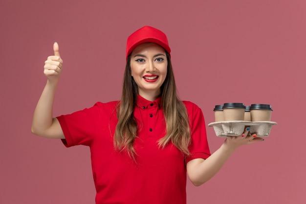 Widok z przodu żeński kurier w czerwonym mundurze, trzymając filiżanki kawy dostawy i uśmiechając się na różowym tle