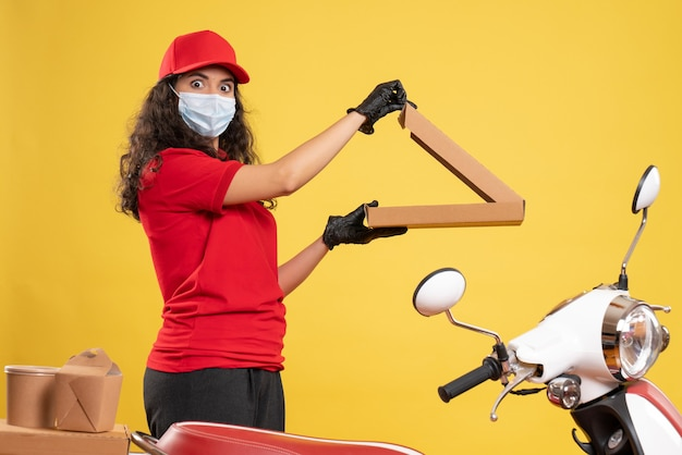 Widok z przodu żeński kurier w czerwonym mundurze z pudełkiem po pizzy na żółtym tle dostawa pracownika covid-pandemiczna usługa wirusa praca
