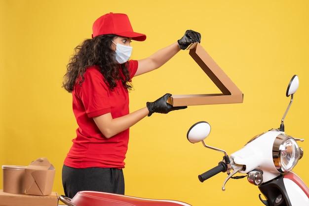 Widok z przodu żeński kurier w czerwonym mundurze z pudełkiem po pizzy na żółtym tle dostawa pracownika covid-usługa wirusowa praca