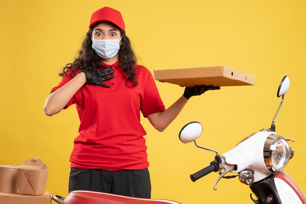 Widok z przodu żeński kurier w czerwonym mundurze z pudełkiem po pizzy na żółtym tle pracownik serwisu covid-wirus dostawa pracy