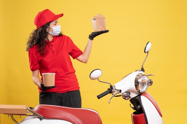 Widok z przodu żeński kurier w masce trzymającej dostawę deser i jedzenie na żółtym tle covid-praca jednolitego pracownika usługi dostawy
