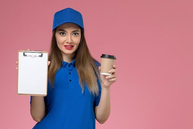 Widok z przodu żeński kurier w niebieskim mundurze i pelerynie trzyma filiżankę kawy dostawy i notatnik uśmiechnięty na różowej ścianie pracownika