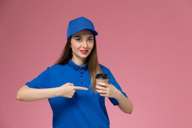 Widok z przodu żeński kurier w niebieskim mundurze i pelerynie trzyma filiżankę kawy dostawy na różowej ścianie kobieta pracownica