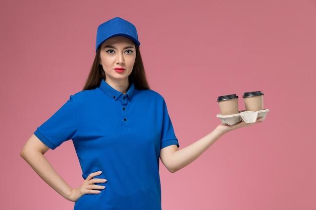 Widok z przodu żeński kurier w niebieskim mundurze i pelerynie trzyma filiżanki kawy dostawy na różowej ścianie kobiet