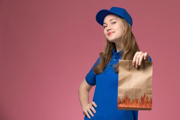 Widok z przodu żeński kurier w niebieskim mundurze trzyma pakiet żywności i pozuje na różowym tle pracownik służbowy firma mundurowa