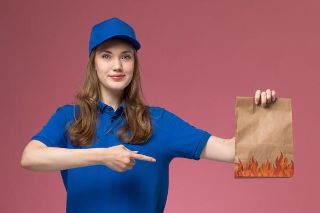 Widok z przodu żeński kurier w niebieskim mundurze trzyma pakiet żywności z lekkim uśmiechem na jasnoróżowym biurku pracownik służbowy mundurowa firma