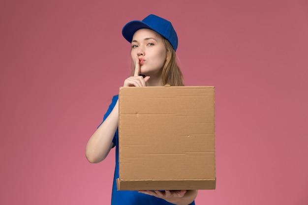Widok z przodu żeński kurier w niebieskim mundurze trzyma pudełko dostawy żywności pokazując znak ciszy na różowym biurku firma mundurowa służb pracy