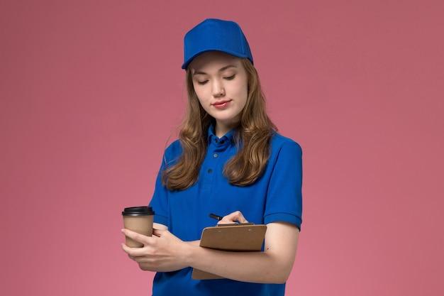Widok z przodu żeński kurier w niebieskim mundurze, trzymając brązowy kubek kawy, zapisując notatkę na jasnoróżowym mundurze biurowym