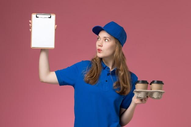 Widok z przodu żeński kurier w niebieskim mundurze, trzymając notatnik i filiżanki kawy dostawy na lekkim biurku