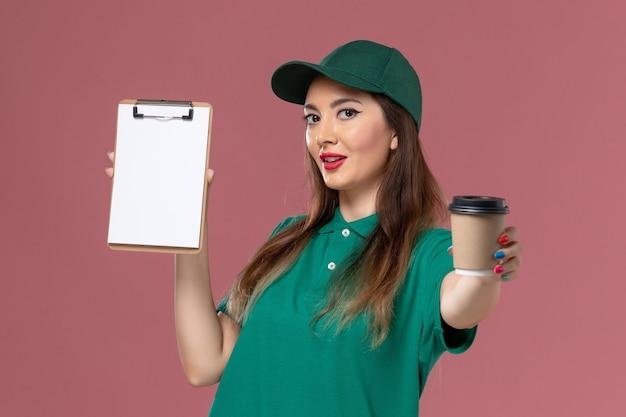 Widok z przodu żeński kurier w zielonym mundurze i pelerynie trzyma dostawę filiżankę kawy i notatnik na różowej ścianie pracownik firmy praca usługa jednolita dostawa pracy