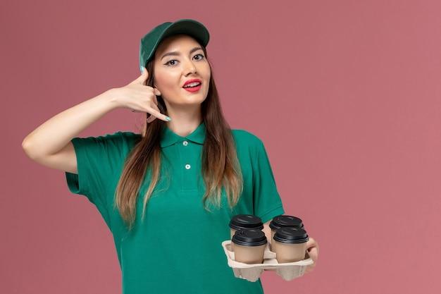 Widok z przodu żeński kurier w zielonym mundurze i pelerynie trzyma dostawę kawy cupson różowa ściana usługowa jednolita praca dostawy firmy