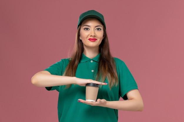 Widok z przodu żeński kurier w zielonym mundurze i pelerynie trzyma filiżankę kawy dostawy na różowej ścianie firma usługowa jednolita praca pracownik dostawy pracy kobiet