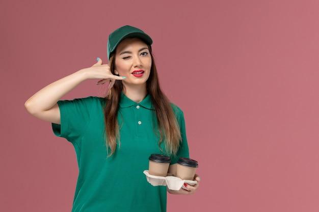 Widok z przodu żeński kurier w zielonym mundurze i pelerynie trzyma filiżanki kawy dostawy na różowej ścianie firma usługowa jednolita praca pracownik dostawy praca kobiet
