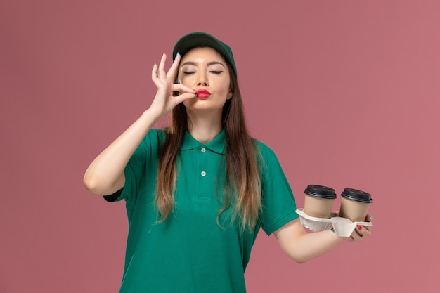 Widok z przodu żeński kurier w zielonym mundurze i pelerynie trzyma filiżanki kawy dostawy na różowej ścianie firma usługowa jednolita pracownik dostawy pracy kobiet