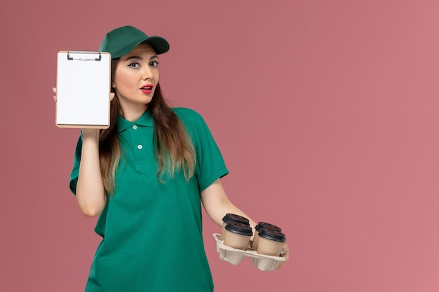 Widok z przodu żeński kurier w zielonym mundurze i pelerynie trzyma notatnik i dostawy filiżanek na różowym biurku jednolity pracownik dostawy
