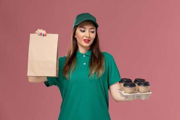 Widok z przodu żeński kurier w zielonym mundurze i pelerynie trzyma pakiet żywności i dostawy filiżanek kawy na różowym biurku jednolita dostawa pracy