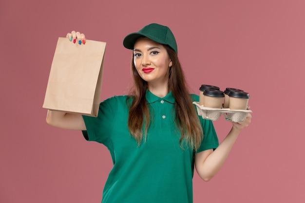 Widok z przodu żeński kurier w zielonym mundurze i pelerynie trzyma pakiet żywności i dostawy filiżanek kawy uśmiechnięty na różowym biurku jednolita dostawa pracy