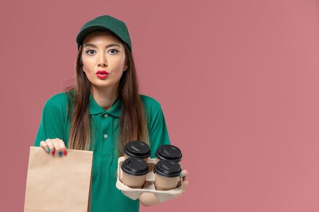 Widok z przodu żeński kurier w zielonym mundurze i pelerynie trzyma pakiet żywności i filiżanki kawy dostawy na różowym biurku jednolita firma dostawy pracy pracownika