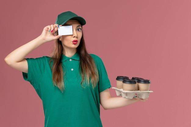 Widok z przodu żeński kurier w zielonym mundurze i pelerynie, trzymając kartę i dostawy filiżanek na różowej ścianie