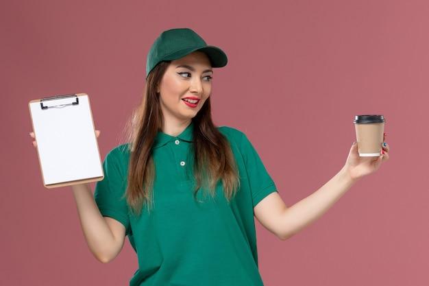 Widok z przodu żeński kurier w zielonym mundurze i pelerynie trzymający dostawę filiżankę kawy i notatnik na różowej ścianie usługi służbowe jednolite dostawy pracy firma pracownik