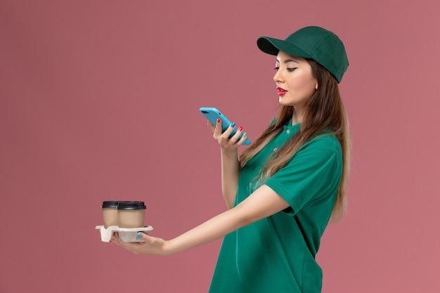 Widok z przodu żeński kurier w zielonym mundurze i pelerynie trzymający dostawy filiżanek do kawy robiąc zdjęcie na różowym backgruond usługa mundurowa dostawa