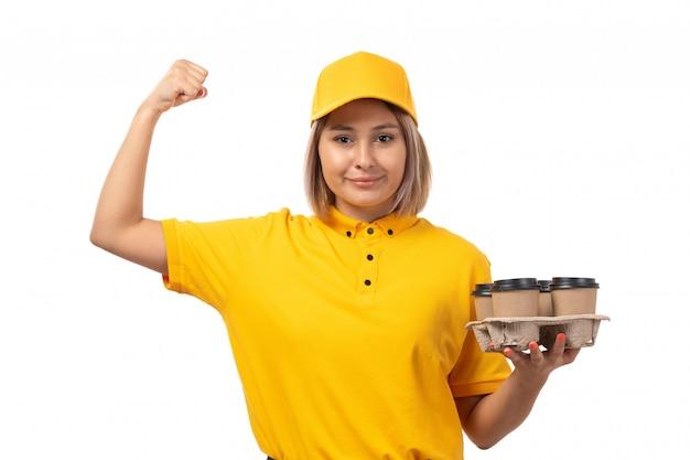 Widok z przodu żeński kurier w żółtej czapce żółtej koszuli trzyma kawę uśmiechnięty na białym tle