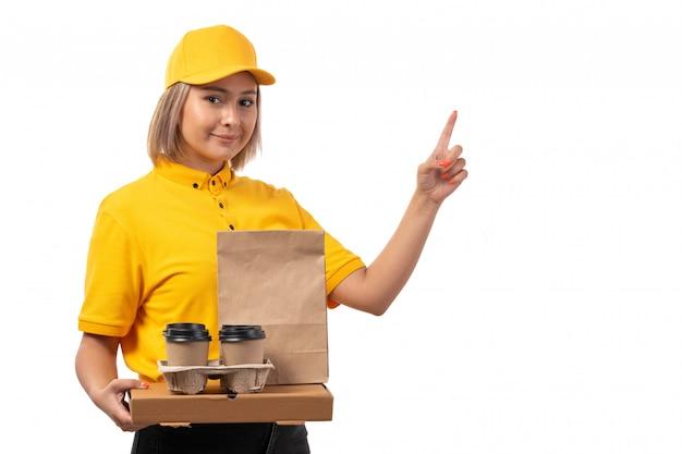 Widok z przodu żeński kurier w żółtej czapce żółtej koszuli trzyma pizzę pudełko kawy uśmiechając się na białym tle