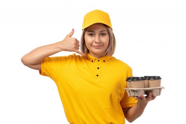 Widok z przodu żeński kurier w żółtej czapce żółtej koszuli, uśmiechając się i trzymając kawę, pozowanie na białym tle