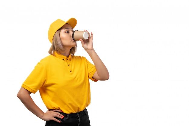 Widok z przodu żeński kurier w żółtej koszuli i czarnych dżinsach pije kawę na białym tle